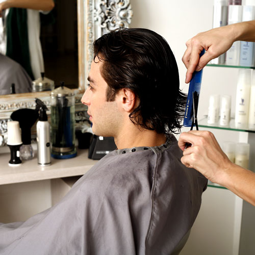 hairdresser cutting a groom's hair in hair salon, pre-groom wedding makeup