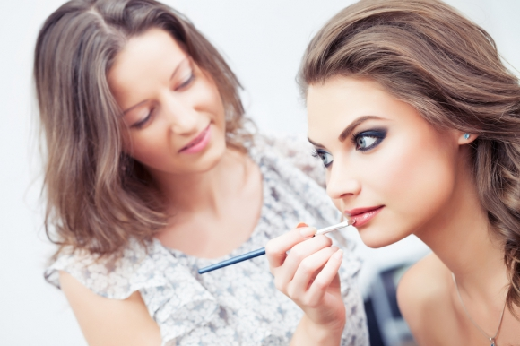 Professional Makeup Artist applying lip liner to a woman for wedding