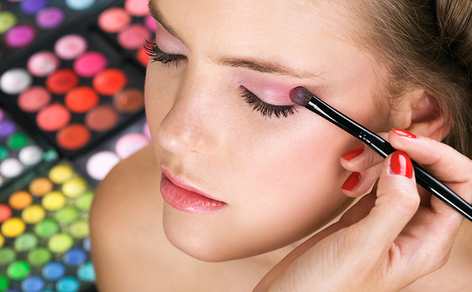 woman applying self eye makeup using eye shadow brush