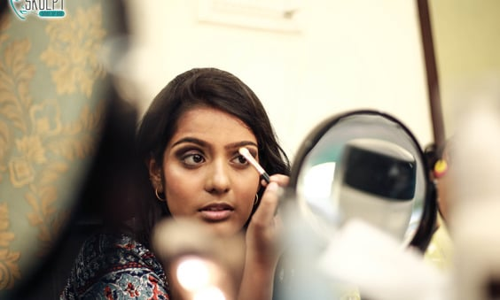 Woman looking at mirror and applying eye shadow with makeup brush, self makeup course