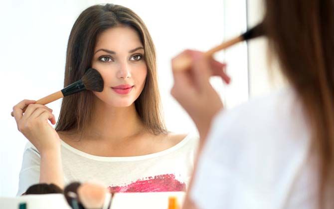woman looking at mirror and applying makeup using makeup brush