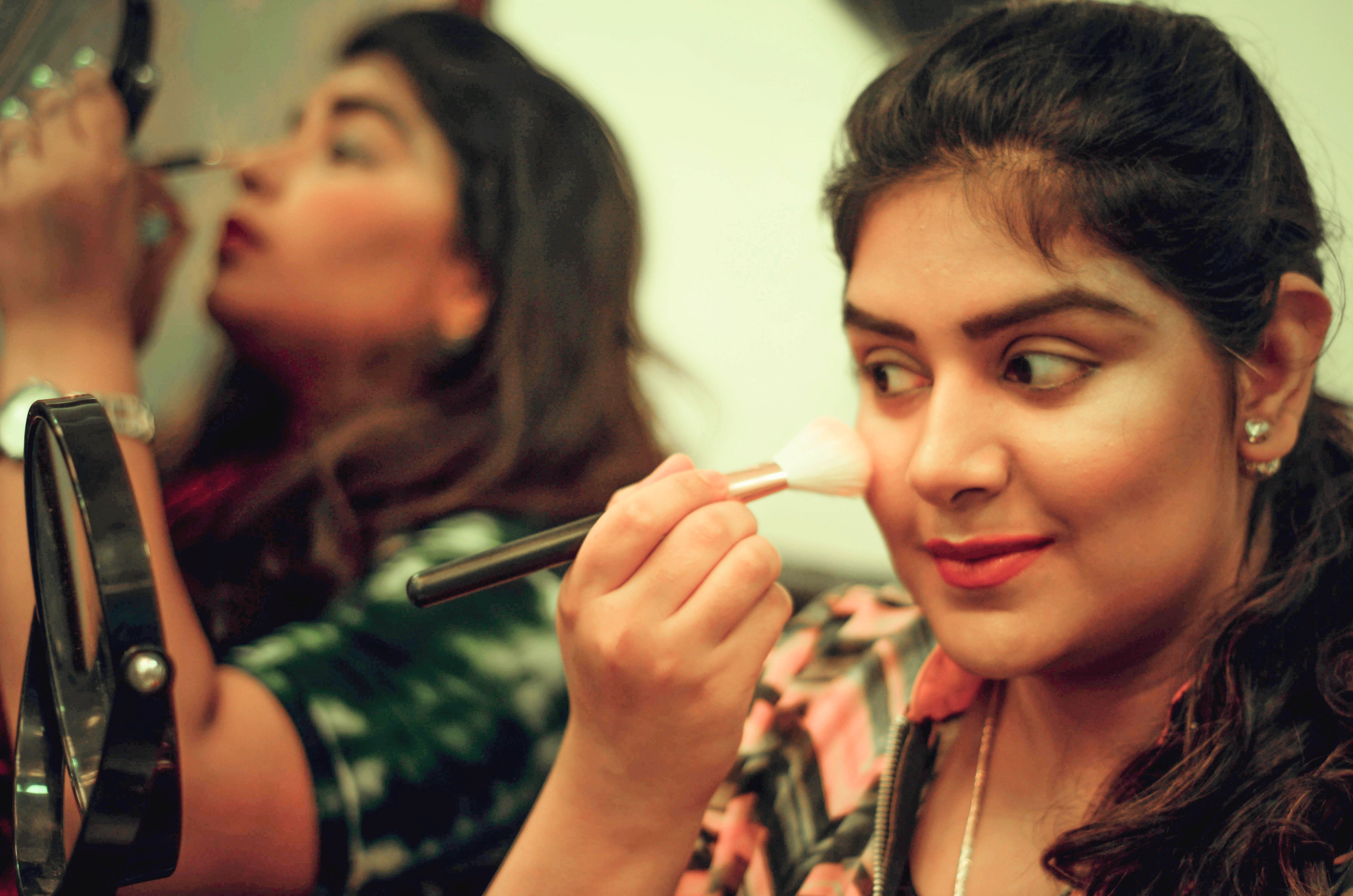 woman applying makeup with blusher