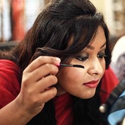 Woman applying mascara with makeup brush