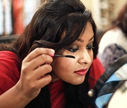 woman holding mascara brush and applying self eye makeup infront of mirror