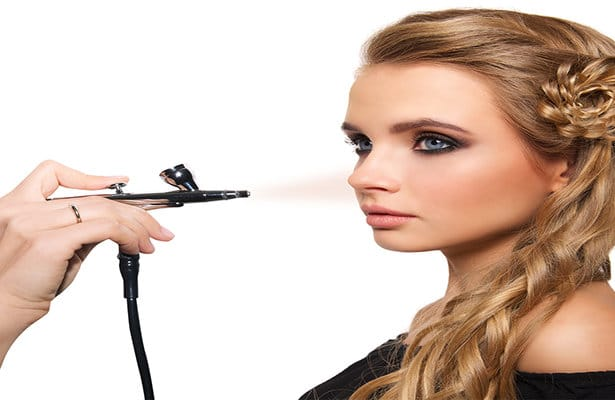 woman applying makeup with airbrush tool in makeup class