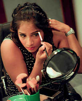 Student in personal makeup class applying eye shadow sitting before makeup brushes & mirror
